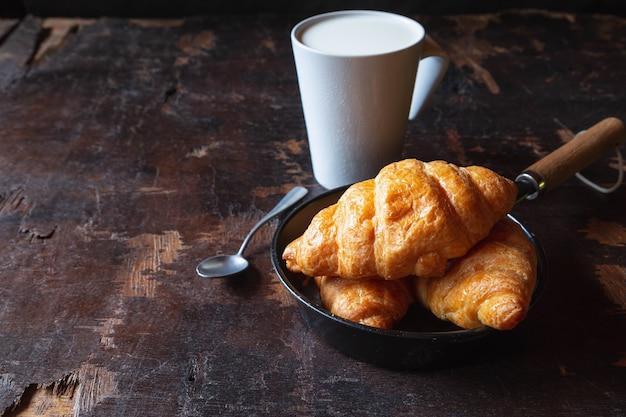 Ontbijtbrood, croissants en verse melk op de houten tafel.