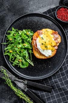 Ontbijtburger met spek, egg benedict, hollandaisesaus op briochebroodje. zwarte achtergrond. bovenaanzicht