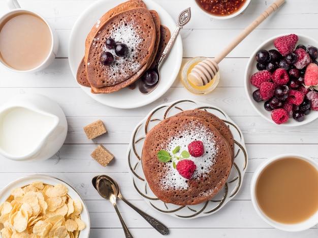 Ontbijtchocoladepannekoeken met bessen, een kop van koffie met room, honing en graangewassen