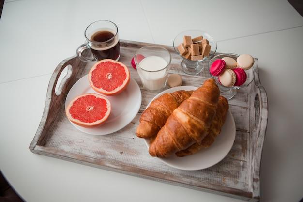 Ontbijtcroissants met koffie op een dienblad