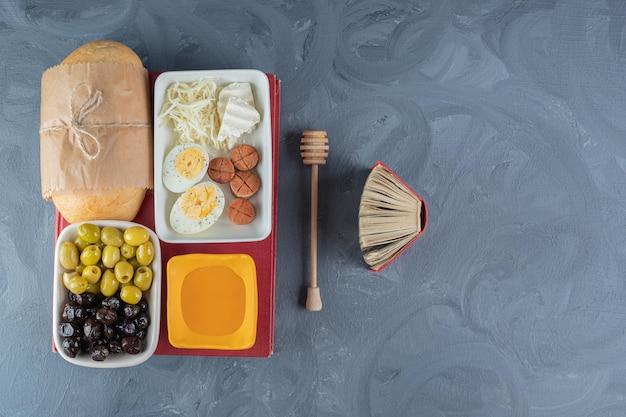 Ontbijtcursus gebundeld bovenop een boek, naast een klein notitieboekje, een honinglepel en een glas sap op een marmeren tafel.