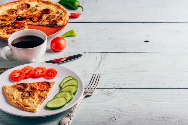 Ontbijtfrittata met chorizo, tomaten en chilipepers op plaat en kopje koffie over lichte houten achtergrond