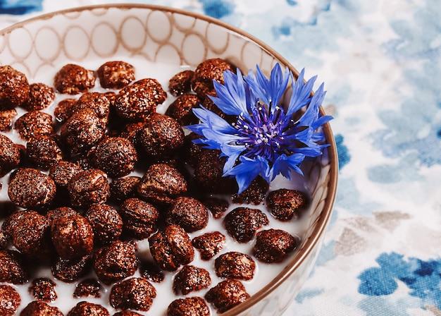 Ontbijtgranen, chocoladegranen in melk met korenbloembloem op een natuurlijk blauw servet, concept van gezonde voeding voor kinderen.