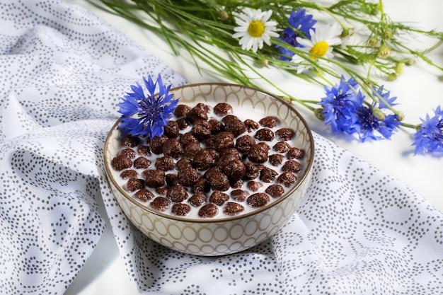 Ontbijtgranen, chocoladegranen in melk met korenbloembloem op een natuurlijk servet, concept gezonde voeding voor kinderen, zachte nadruk.