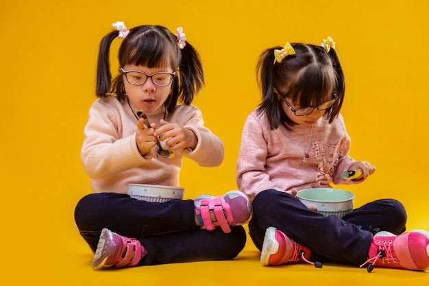 Ontbijtgranen eten. nauwkeurige schattige jonge meisjes met het syndroom van down die metalen lepels dragen en een licht ontbijt hebben