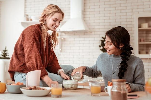 Ontbijtgranen. vrolijke blonde vrouw in oranje oversized trui zittend op tafel terwijl haar vriend melk deelt