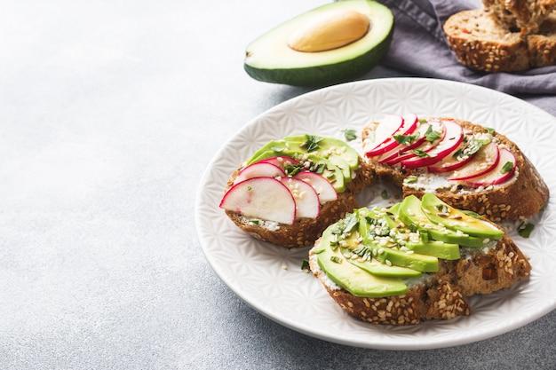 Ontbijtgranenbroodjes met kwark, verse avocado en radijs.