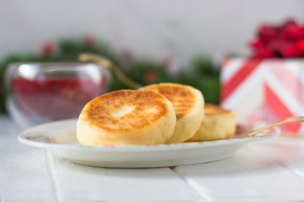Ontbijtkaaspannekoeken en frambozenjam op een achtergrond van dennentakken met kegels en rode bessen en een geschenk