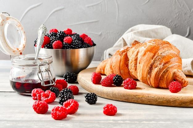 Ontbijtkoffie met melk en croissants, jam en verse frambozen en bramen