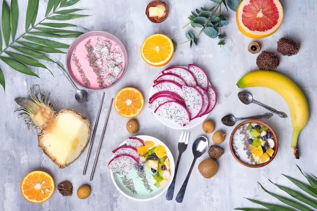 Ontbijtlijst met de kommen van de yoghurtaardbei smoothie en verse tropische vruchten op een grijze steenachtergrond. acai kom wilde bessen en fruit smoothie kom, plat leggen