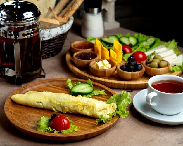 Ontbijtopstelling met omelet en bijgerechtenbord