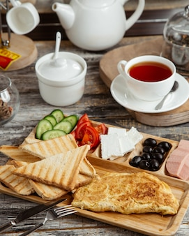 Ontbijtopstelling met omelet toast komkommer tomaat kaas olijf en thee