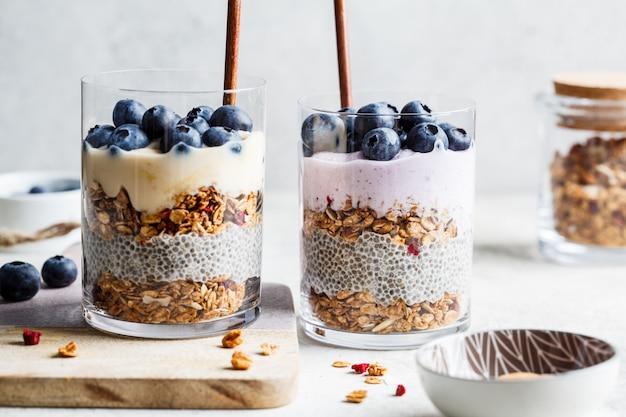 Ontbijtparfait met chia, granola, bessen en yoghurt in een glas. laagdessert in glas.