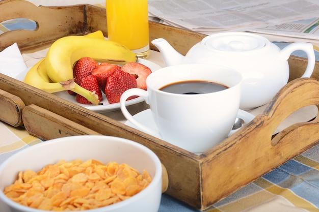 Ontbijtplateau met koffie, jus d'orange, ontbijtgranen en fruit.