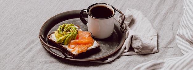 Ontbijtsandwiches met zalm en avocado op bed