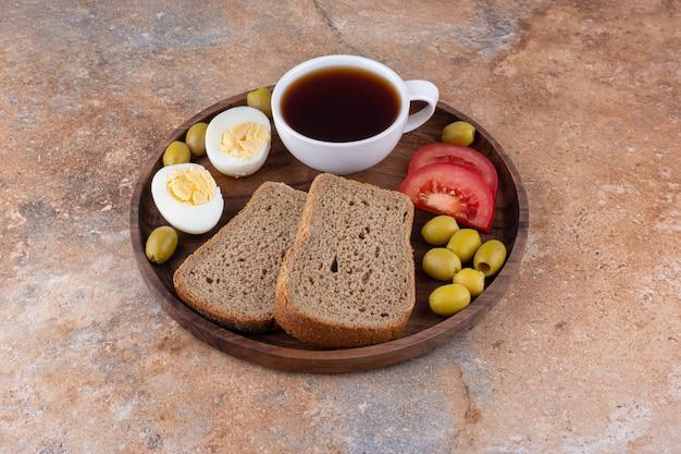 Ontbijtschotel met brood en een kopje thee