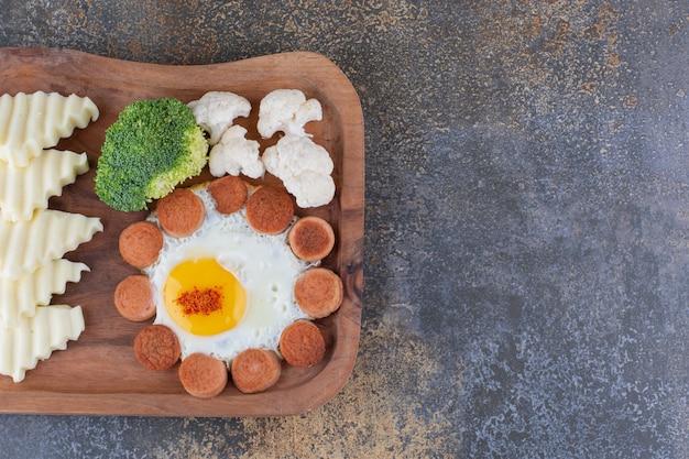 Ontbijtschotel met gebakken ei, worstjes en overige ingrediënten