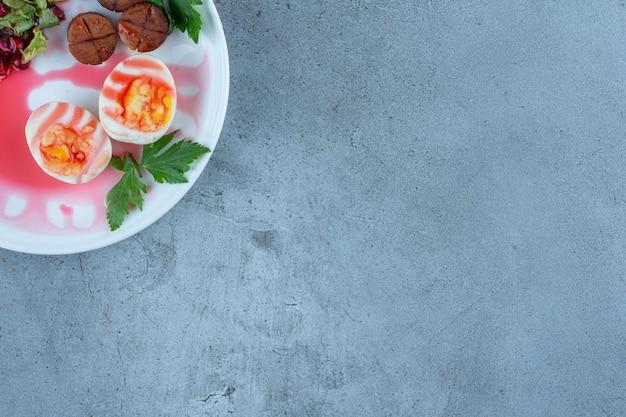 Ontbijtschotel van gekookte eieren, gebakken worstplakken en een klein deel van granaatappelsalade op marmer.