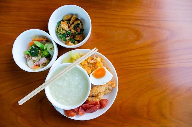 Ontbijtset, gekookte rijst in een kom, geroerbakte groenten, gebakken gehaktballen met basilicum