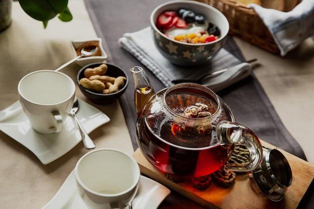 Ontbijtset havermout met bessen en zwarte thee met roze bloemen