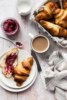Ontbijtset plat gelegd met voedselfotografie van croissants en frambozenjam