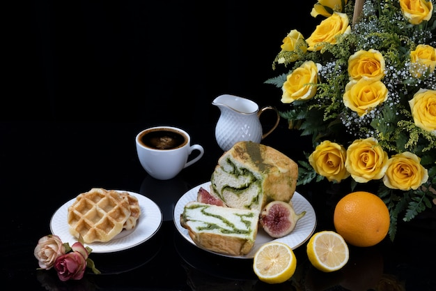Ontbijttafel bestaande uit wafels, matcha brood vijg, sinaasappel en zwarte koffie.