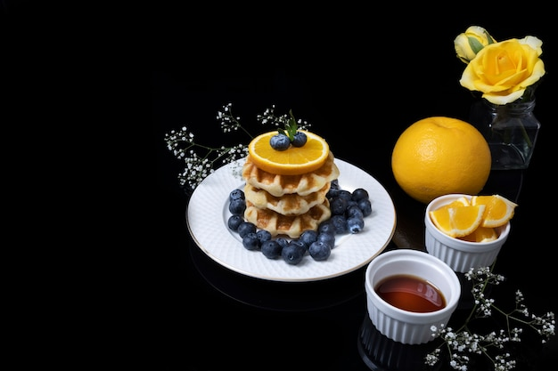 Ontbijttafel bestaande uit wafels met honing, bosbessen en sinaasappel.