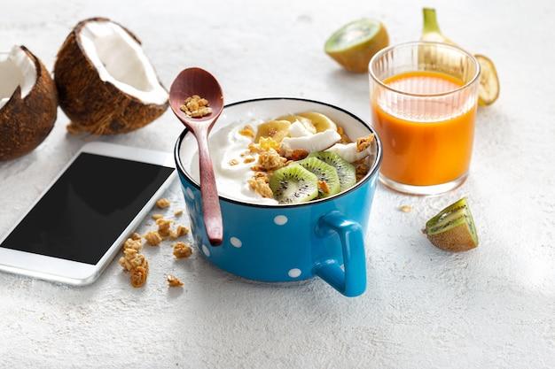 Ontbijttafel concept. smartphone met ã'â kokos yoghurt met granola en fruit op lichte thuis tafel met met wortel appelsap