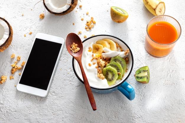 Ontbijttafel concept. smartphone met kokos yoghurt met muesli en fruit op lichte huis tafel met met wortelsap