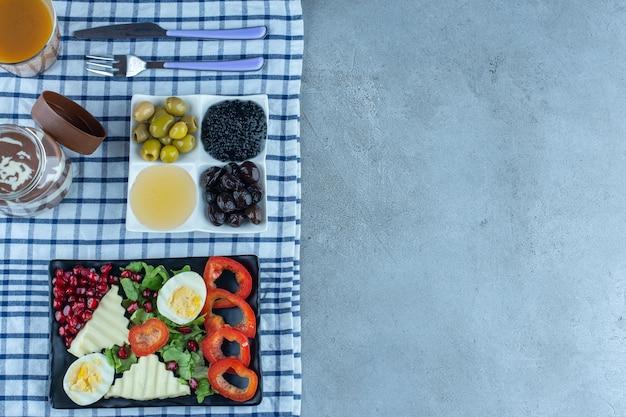 Ontbijttafel gemaakt van porties kaviaar, olijven, honing, kaas, eieren, granaatappel, paprika, chocolade en koffie op marmeren ondergrond