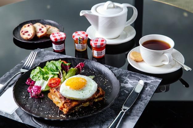 Ontbijttafel instelling, gebakken sandwich met salade en omelet