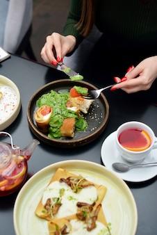 Ontbijttafel instelling met pannenkoeken, thee. stel eet