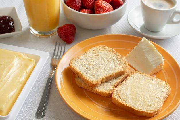 Ontbijttafel met boter, toast, jam en aardbeien.
