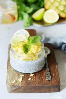 Ontbijttafel met chia fruit smoothies kom met stukjes ananas, limoen, honing en muntblaadjes. gezond voedsel. bovenaanzicht, lege ruimte