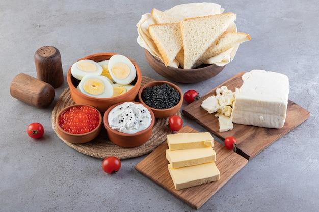 Ontbijttafel met eieren, brood, boter en kaviaar.