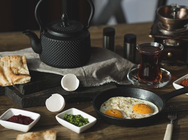 Ontbijttafel met gebakken eieren, kruiden en glas thee