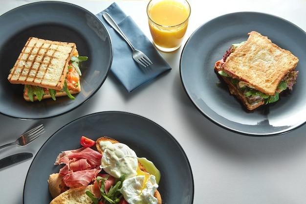 Ontbijttafel met gezonde voeding. toast sandwich, benedict eieren, spek, sinaasappelsap en groenten