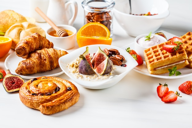Ontbijttafel met havermout, wafels, croissants en fruit.