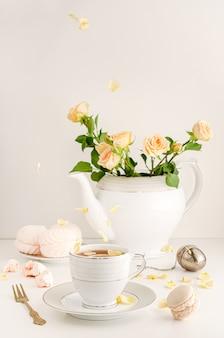 Ontbijttafel met rozen, vliegende bloemblaadjes, macaron en schuimgebakjes