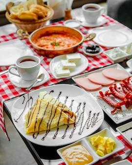 Ontbijttafel met worst, kaas, menemen en pannenkoeken.