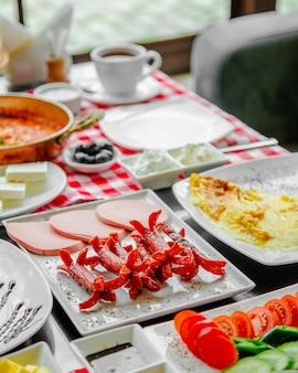 Ontbijttafel met worstjes en ham.