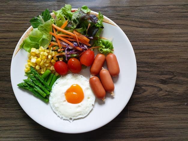 Ontbijttijd gebakken ei met worstjes en groenten zoals tomatenstoommais asperges