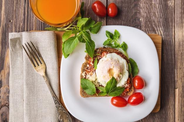 Ontbijttoost met gepocheerd ei, tomatensaus, basilicum en parmezaanse kaas op houten achtergrond