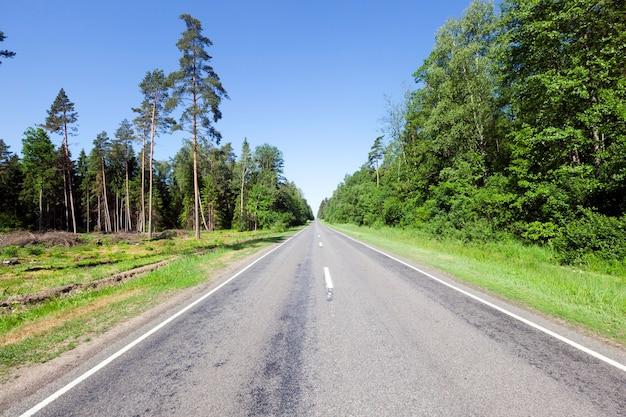 Ontbossing en houtkap in de buurt van een auto-verharde weg in de zomer, een blauw luchtlandschap met zonnig weer