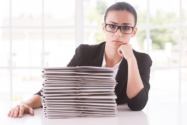 Ontbrekende deadlines. depressieve jonge vrouw in pak die naar de camera kijkt en het hoofd op de kin houdt terwijl ze aan de tafel zit met een stapel documenten erop
