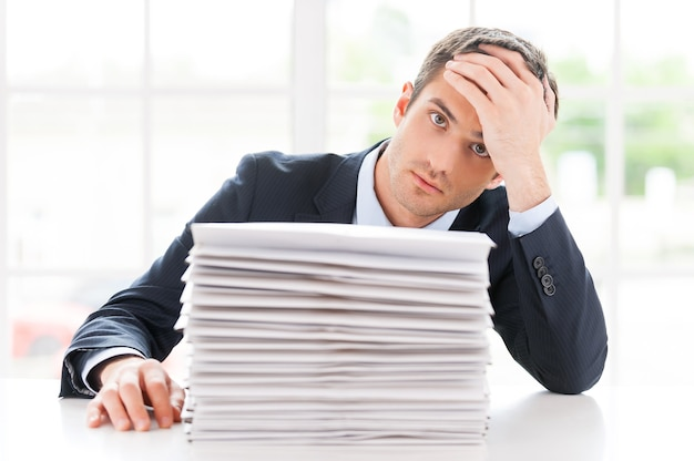 Ontbrekende deadlines. depressieve jongeman in overhemd en stropdas die naar de camera kijkt en het hoofd in de hand houdt terwijl hij aan de tafel zit met een stapel documenten erop