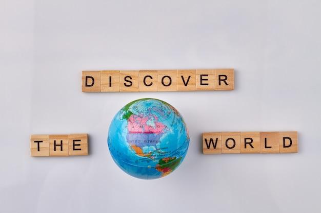 Ontdek de wereld gemaakt van houten letterblokken. globe en letter kubussen op witte achtergrond.