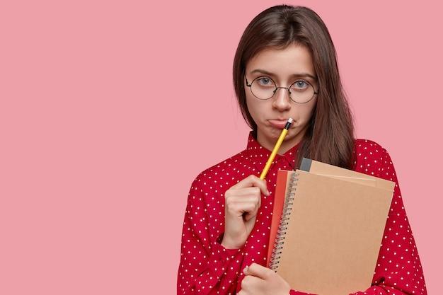 Ontevreden aantrekkelijke jonge dame schrijft records in blocnote, draagt een spiraalvormig notitieboekje, heeft een ronde grote bril