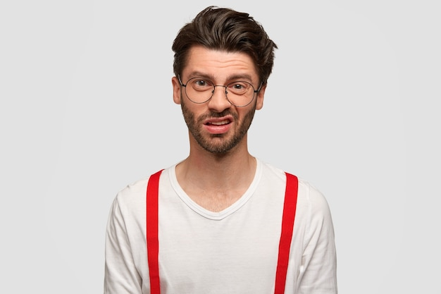 Ontevreden aantrekkelijke jonge mannelijke hipster heeft een verbaasde uitdrukking, fronst zijn gezicht, kijkt met afkeer, merkt iets onaangenaams op, draagt een wit overhemd met rode bretels. gezichtsuitdrukkingen concept.