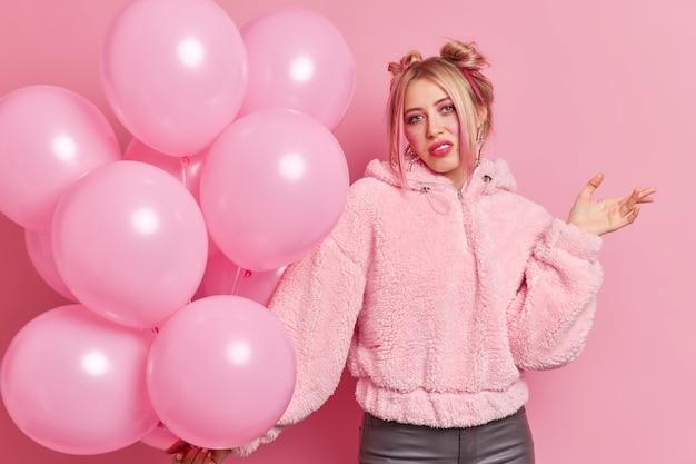 Ontevreden aarzelend blonde jonge vrouw steekt handpalm heeft geen idee van uitdrukking weet niet hoe ze haar jubileum moet vieren